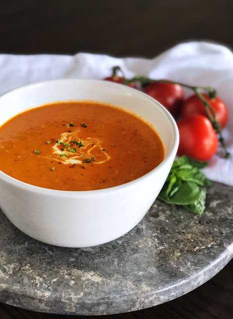 Roasted Tomato Soup in a white bowl garnished with cream and herbs