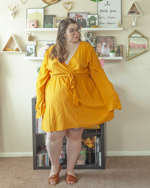 An outfit consisting of a mustard yellow wrap dress with long angel sleeves and brown d'orsay sandals.