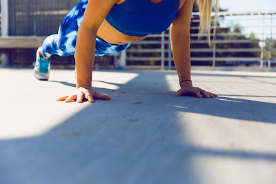 A woman in exercise gear planks on concrete