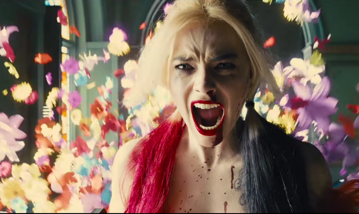 Imagem de capa: a Arlequina, interpretada por Margot Robbie, com os cabelos longos dividos e com mechas vermelhas e pretas, em um vestido vermelho, gritando, com o nariz sangrando e dezenas de flores explodindo às suas costas.