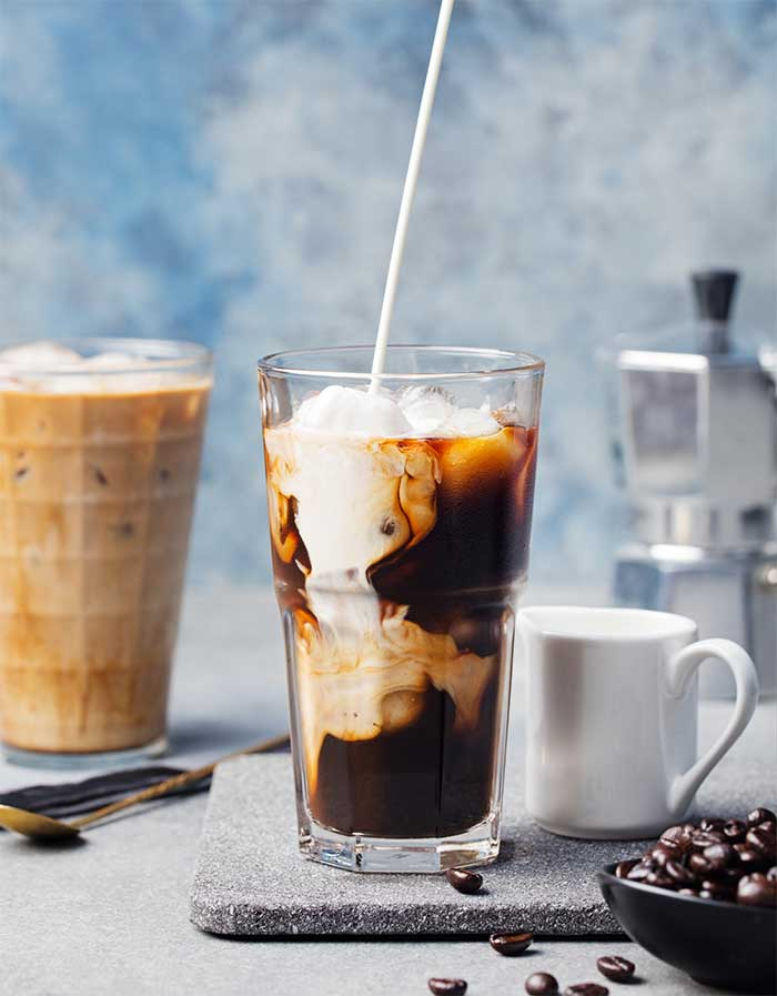 How to make a skinny iced vanilla latte at home. This easy recipe has coffee, a skinny vanilla simple syrup, and milk.  You can make it with almond milk, coconut milk, or cow's milk. This is inspired by Starbucks, but it's under 200 calories and gluten free, low carb, and great for clean eating.  DIY iced coffee and skinny drinks for a healthy homemade drink. #vanilla #icedcoffee