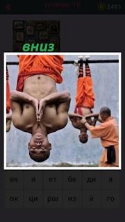 вниз головой висят несколько монахов с голым торсом сложив руки
