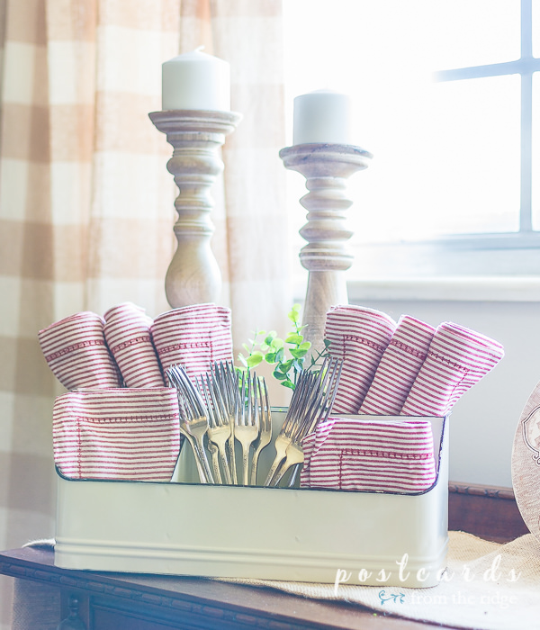 vintage silver forks and red stripe napkins in a enamel caddy