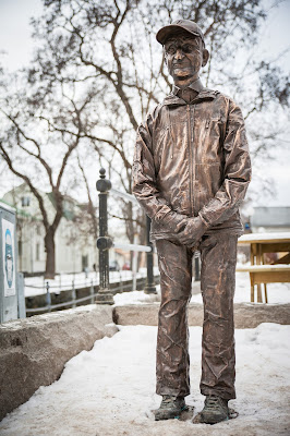 A bronze statue of a small man, smiling and standing with his hands folded, surrounded by dirty snow. Photographer: Björn Lans/Balansfoto
