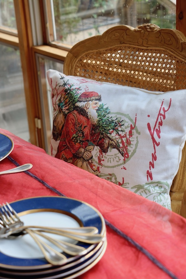 An old-world Santa print in red and green decorates a soft pillow on a French Country dining chair around the Christmas Red and Navy Blue Table Setting
