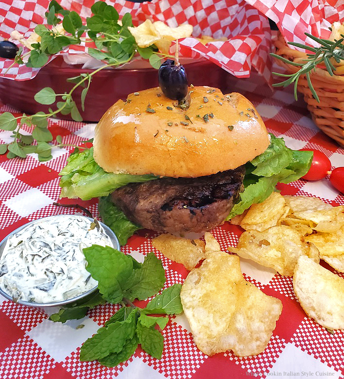 This is a grilled lamb burger with lettuce and spinach tzatziki sauce on the side also potato chips on a checkerboard tablecloth