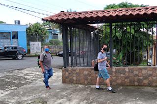Two masked men on sidewalk in Santiago de Puriscal