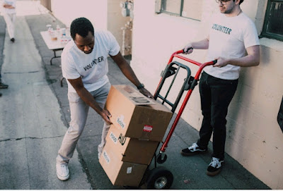 Two men handling a dolly with two cardboard boxes on it.