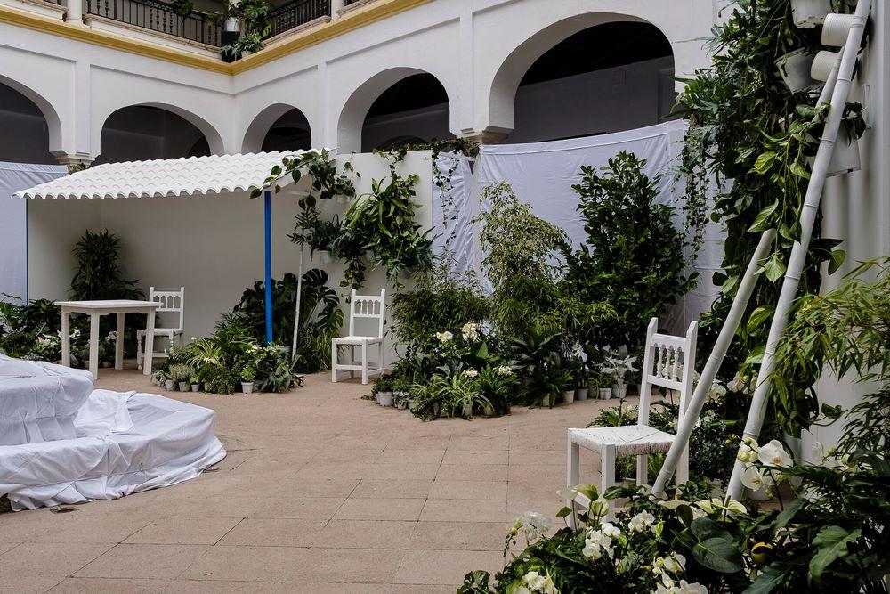 Patio blanco con sillas y mesas blancs y plantas verdes con flores blancas