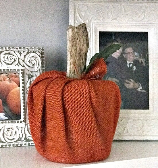 Orange burlap pumpkin on shelf with frames.
