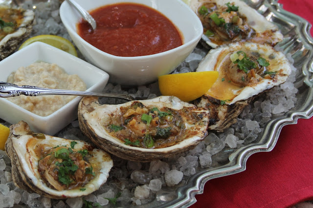 Freshly shucked Gulf oysters, grilled in the shell, with a lemon and garlic butter sauce, and served on an ice or rock salt covered platter with cocktail sauce, horseradish, lemon wedges and hot sauce and French bread on the side.