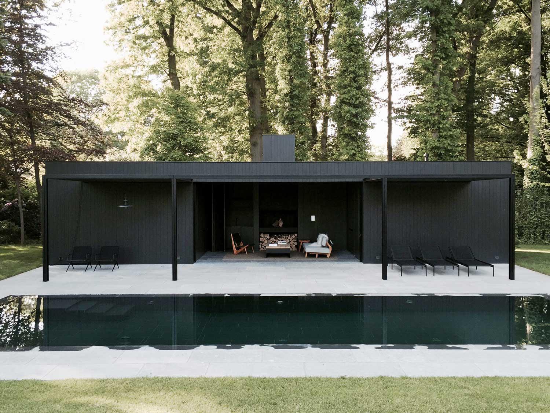 Casa con struttura estera nera e piscina nel bosco by marc merckx