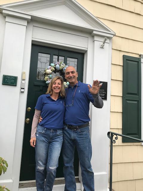 couple in front of front door, waving