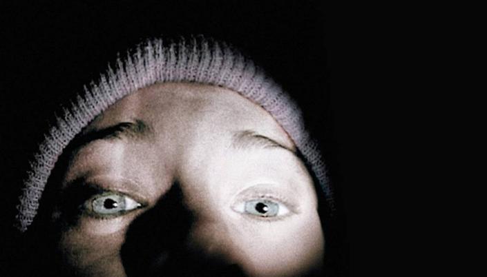 """Imagem: Filme """"Bruxa de Blair"""", mulher branca de olhos azuis, está com o rosto bem próximo, de forma que só é possível ver do seu nariz pra cima. Ela usa toca na cabeça e está com expressão de horror."""