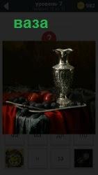 На столе на подносе стоит серебряная ваза и рядом положены красные яблоки
