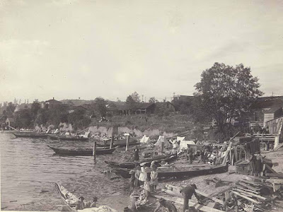 black & white photo - about 5 long canoes pulled onto shore, with men and women occupied on shore; building in background