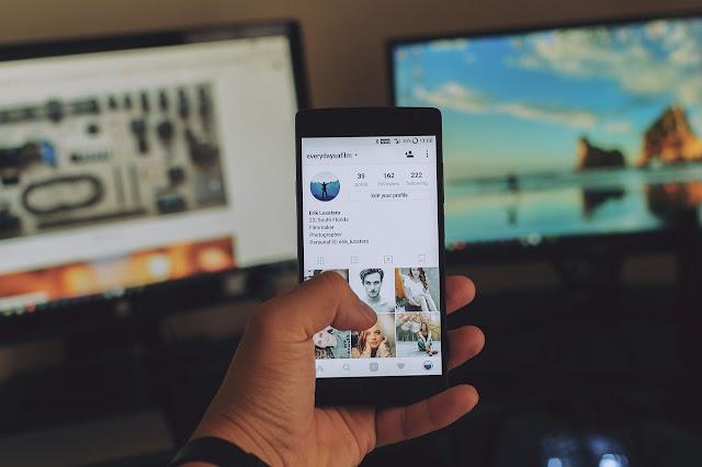 tangan seseorang yang memegang smartphone dengan tampilan layar profil instagram