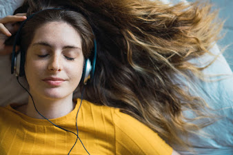 A brunette caucasian woman laid with her hair splayed out wearing headphones