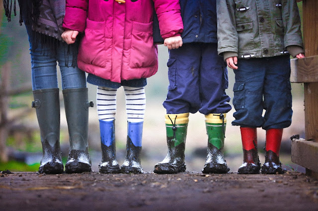 Children standing in a row, holding hands, but the camera is focused on their muddy wellies