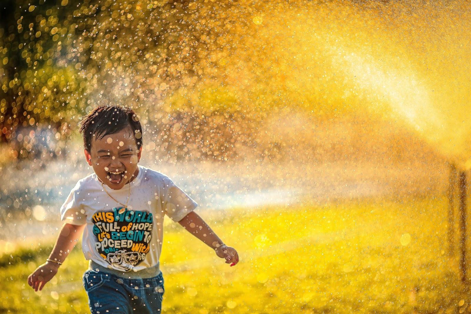 boy running through water sprinkler