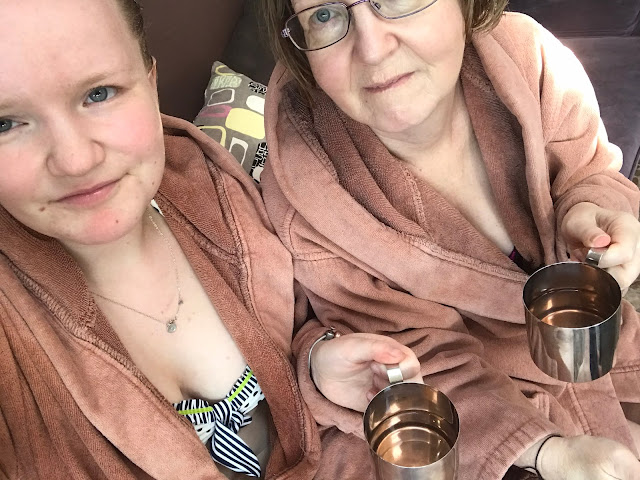 2 Women holding metal mugs