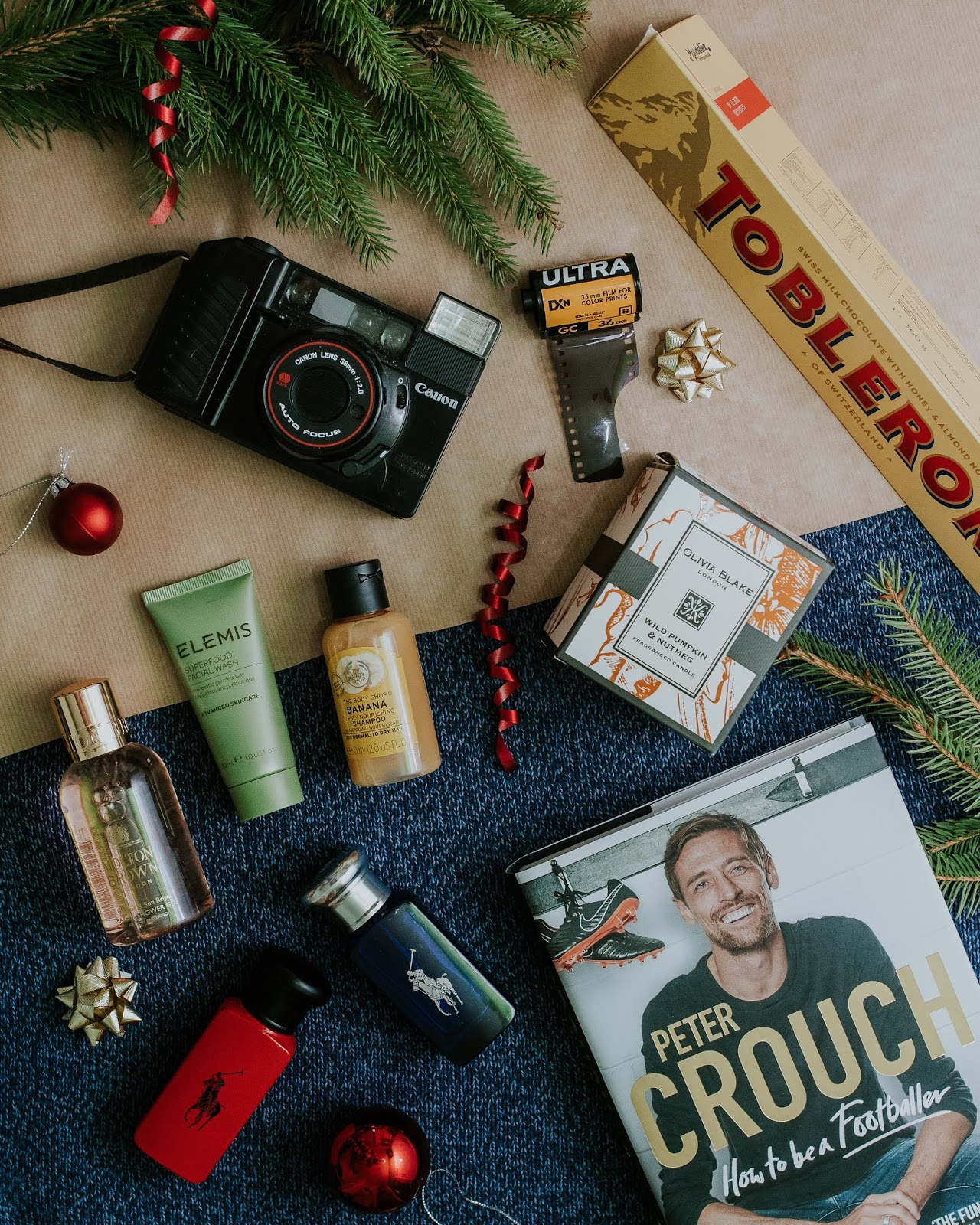 Christmas gift guide for men featuring: ralph lauren red aftershave gift set, a peter crouch book, elemis skincare, the body shop mini shampoo, 35mm film camera, tkmaxx candle
