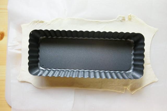 冷凍パイシートをクッキングシートの上にのせ、1枚と1/2枚を2㎝程度重ね、その上にもう1枚クッキングシートをかぶせて麺棒などで型よりやや大きめになるように平らに伸ばします。