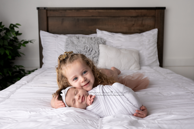 Newborn and sibling photos Eugene OR, big sister cuddling new baby on white bed