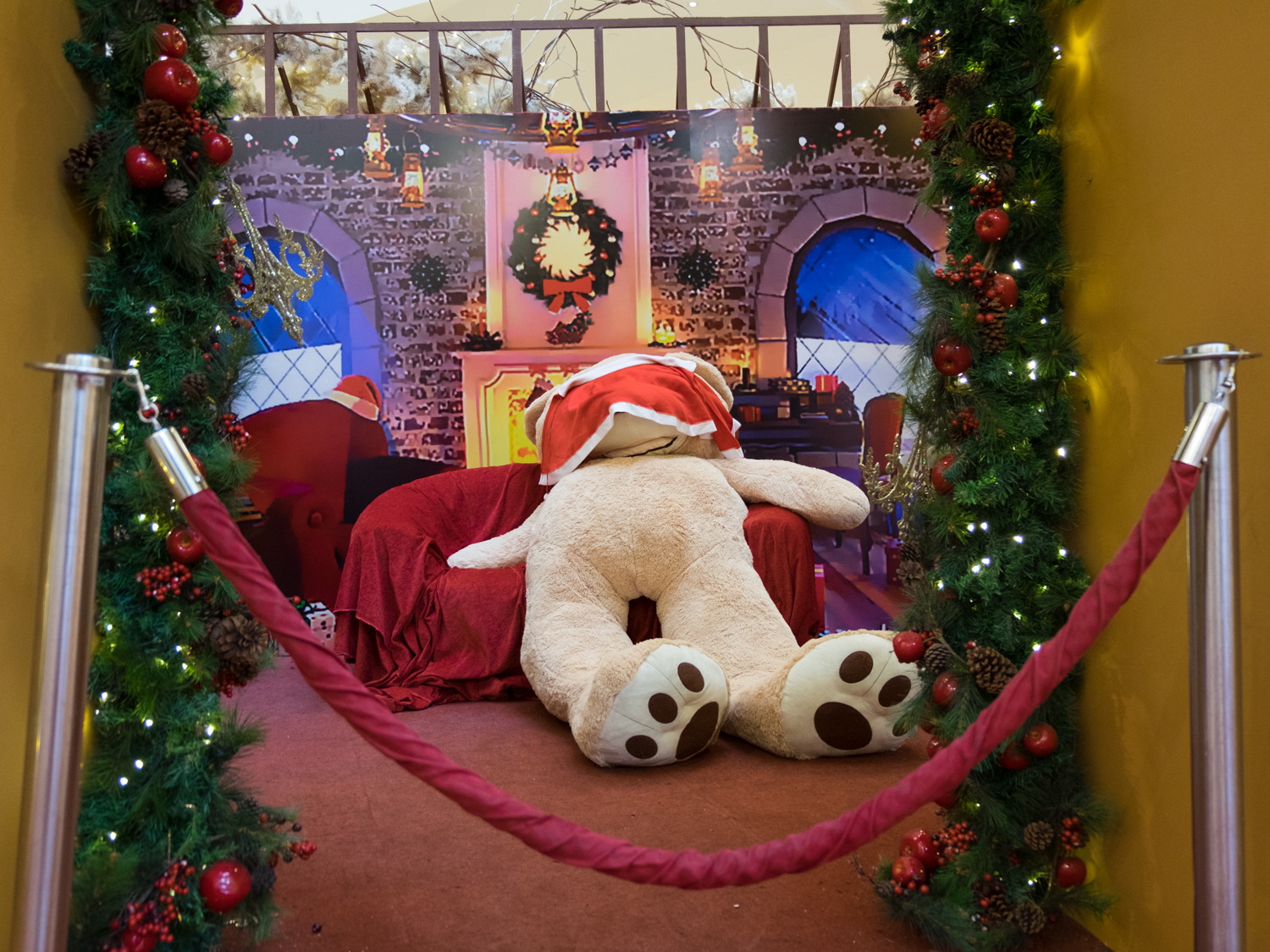 a giant bear collapsed behind ropes taking a break from hours of posing with kids its so hard to be an inanimate object - Giant Christmas Hours