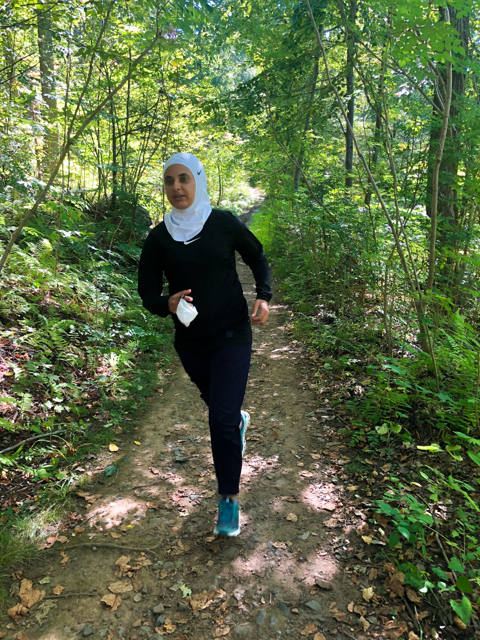 Sahara running on trail, trees around path, mask in hand