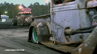 A pink rat rod truck burns the tire completely off the rim.