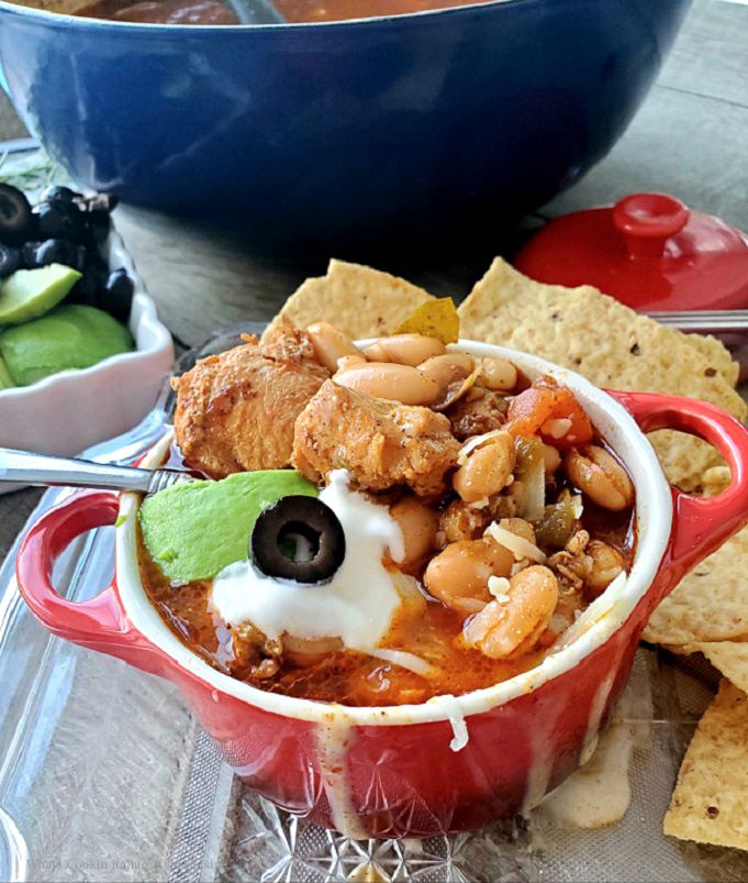 this is a bowl of chicken chili topped with olives, sour cream and avocado with tortilla chips