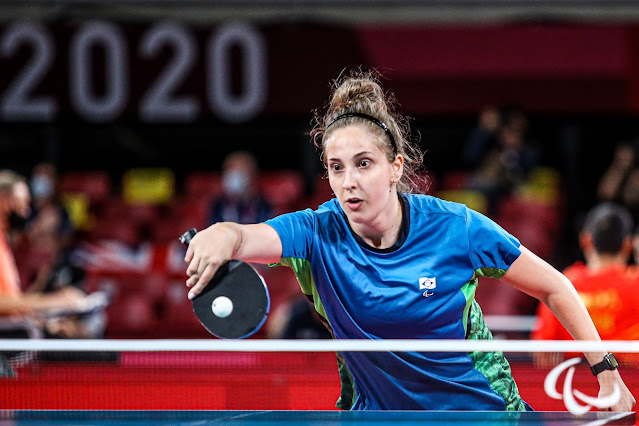 A atleta Daniele Rauen, loira e branca, está vestida de azul e segura a raquete com a mão direita, rebatando a bola da cor branca. Na foto, há também a mesa que é azul