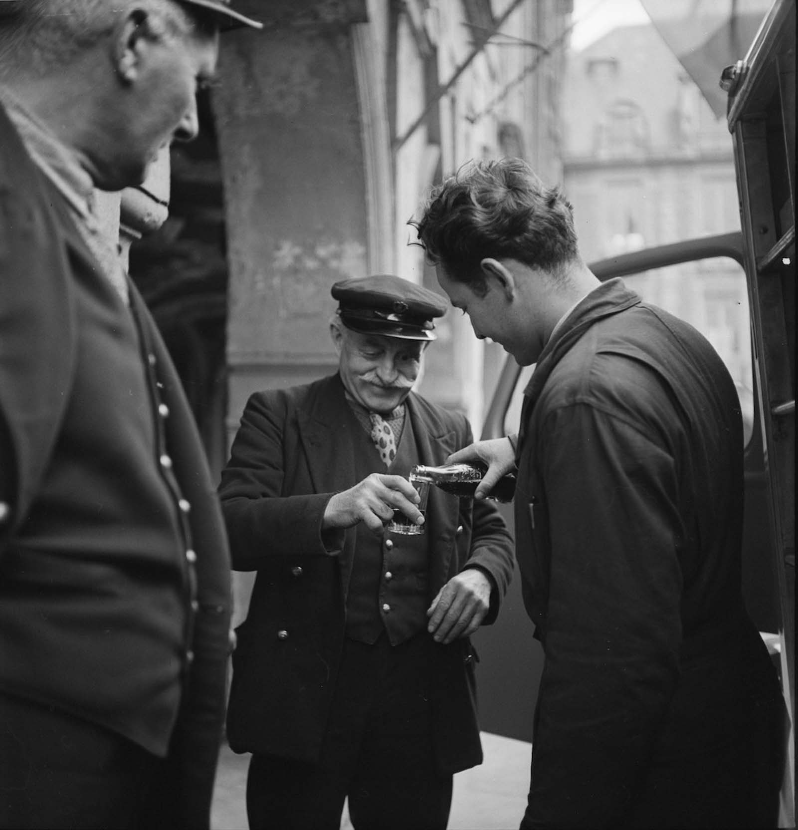 A bystander watches as a man pours a bottle of Coca-Cola into a glass held by a smiling, elderly man, in Paris, France.