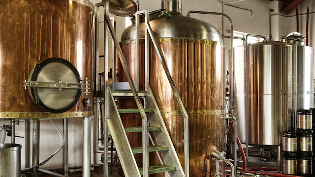 several copper brewing tanks so large that a ladder is needed