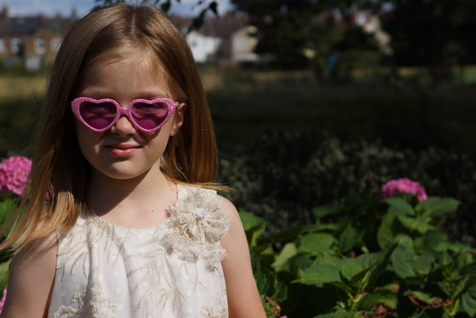 girl with pink heart sunglasses and corsage on David Charles Childrenswear dress