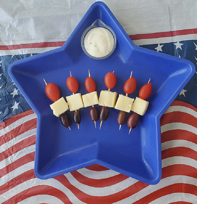 this is a blue star plastic dish with tomato, mozzarella and olive skewers with homemade ranch dressing in a small dish