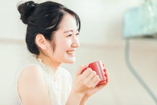 温かい飲み物を飲んで笑っている女性のイメージ