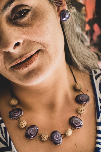 Mulher com semblante sereno usando gargantilha de cerâmica