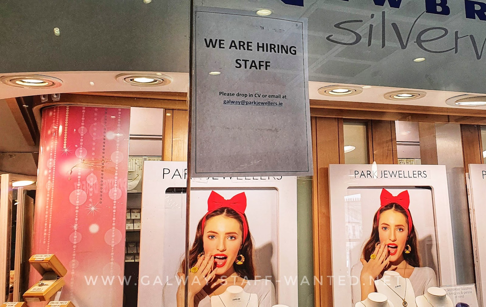 Jewellery store window in Galway city shopping centre, picture of a girl with a bright red ribbon and bow on the top of her head, pointing out like bunny ears
