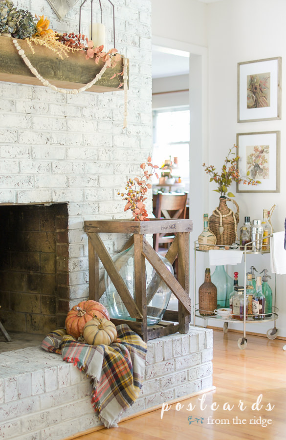 white brick fireplace with fall decor including large glass wine jug in crate