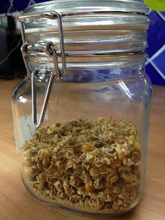 Glass jar containing dried camomile flowers