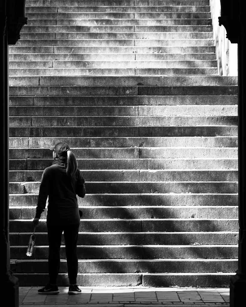 a black and white photo of a woman on a staircase at bethesda terrace new york city