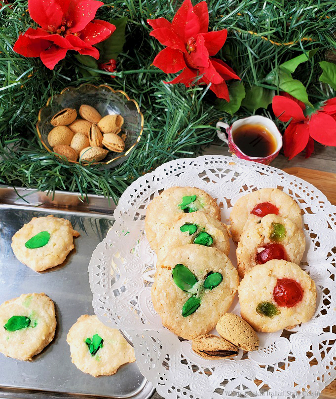 these are Italian cookies made with almond paste with green tinted almonds on top and some have candied red and green cherries for Christmas with nuts and black coffee and lots of holly in the background