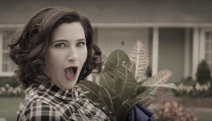 Imagem: cena em sépia de Agatha com um vestido e roupa de época, batom vermelho, olhando para a câmera com uma expressão de fingida surpresa.