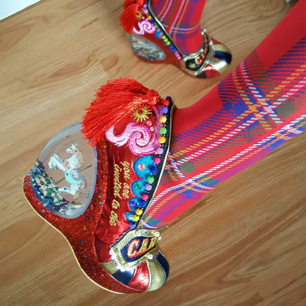 close up of carousel horse in heel of shoe with red tassel and embroidery being worn