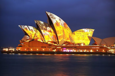 """The Sydney Opera House with its wings lit up with images of Australian firefighters (AKA """"Firies"""")"""