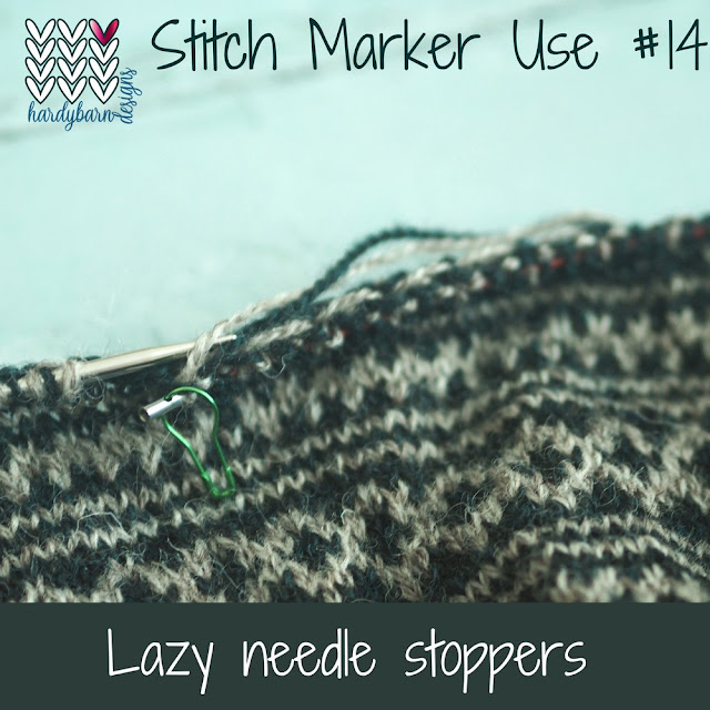Stranded knitting in navy and grey on circular needles with one tip missing and marker in the keyhole