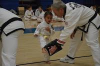 A martial arts toddler girl kicking a target with a black belt