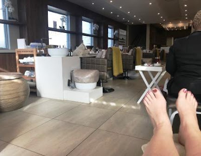 Pedicured feet with J's Revive Spa in background